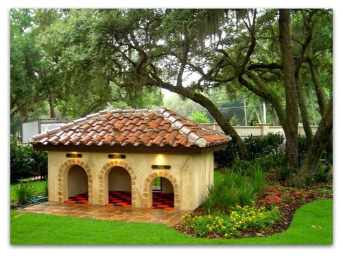 This Mediterranean style dog house has three entrances to the communal space, two large and one small. A mature tree above provides needed shade on hot, sunny days.