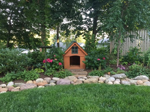 This cabin-style dog house in cedar and forest green fits perfectly into the lush landscaping.