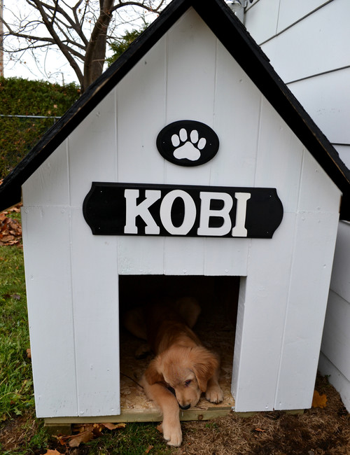 A traditional dog house with a large interior area and a cute sign with the dog's name on it.
