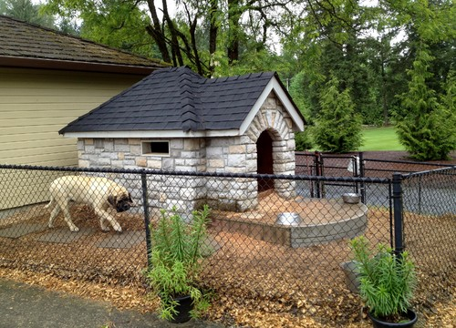 This impressive stone dog house is surrounded by a tall chain link fence to keep a much larger dog in. The structure is comfortable and attractive enough for a backyard.