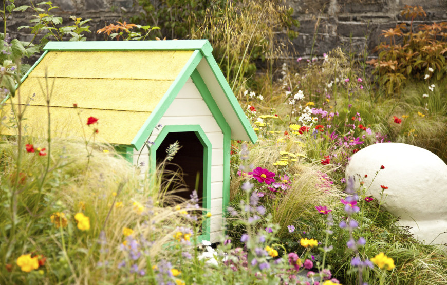 A brightly colored simple dog house fits perfectly into the landscaping of this cottage style garden.