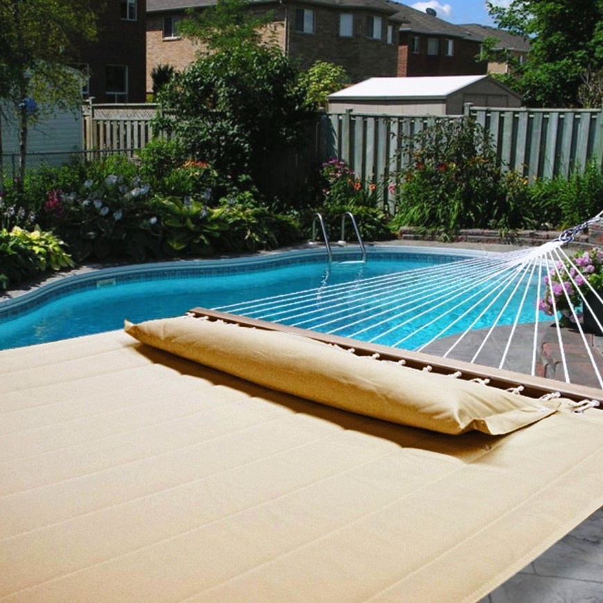 A large quilted cotton hammock by the side of a pool. The spreader bar ensures that it's easy to get into, but it's also easier to fall off the hammock while drifting off for a nap.