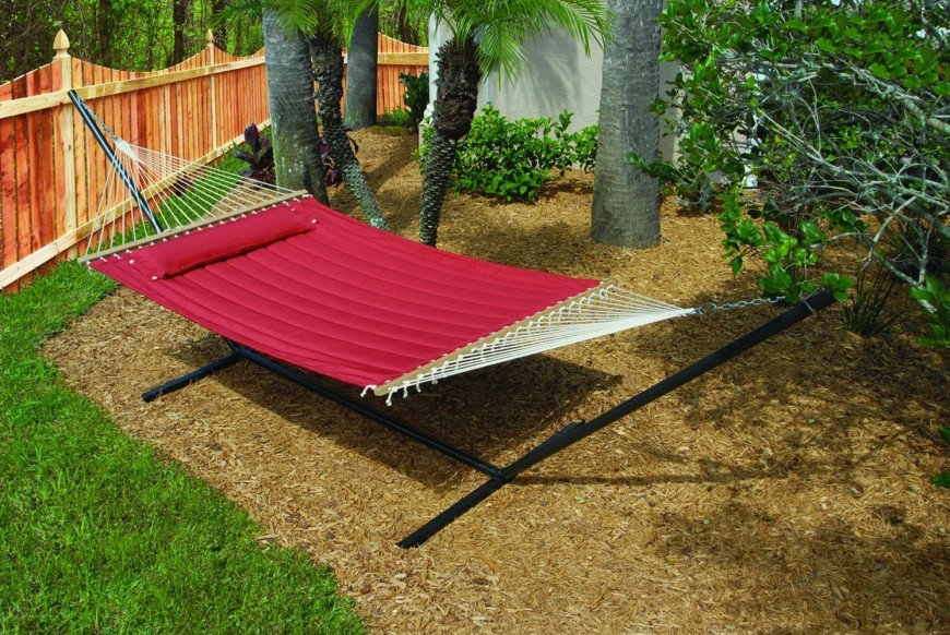 Another quilted hammock suspended on a freestanding metal frame. It's positioned over a mulched section of landscaping and shaded by several tall trees.