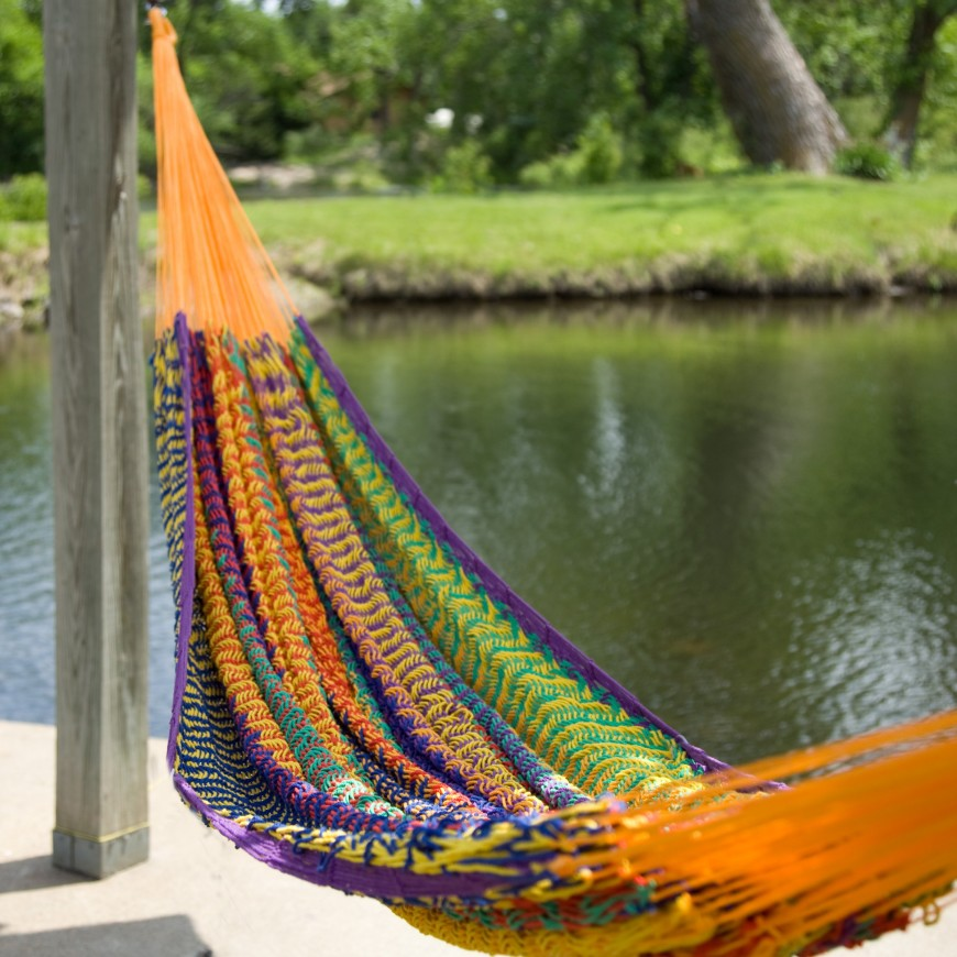 A super colorful Mayan style hammock suspended between two patio supports and looking over a small pond.