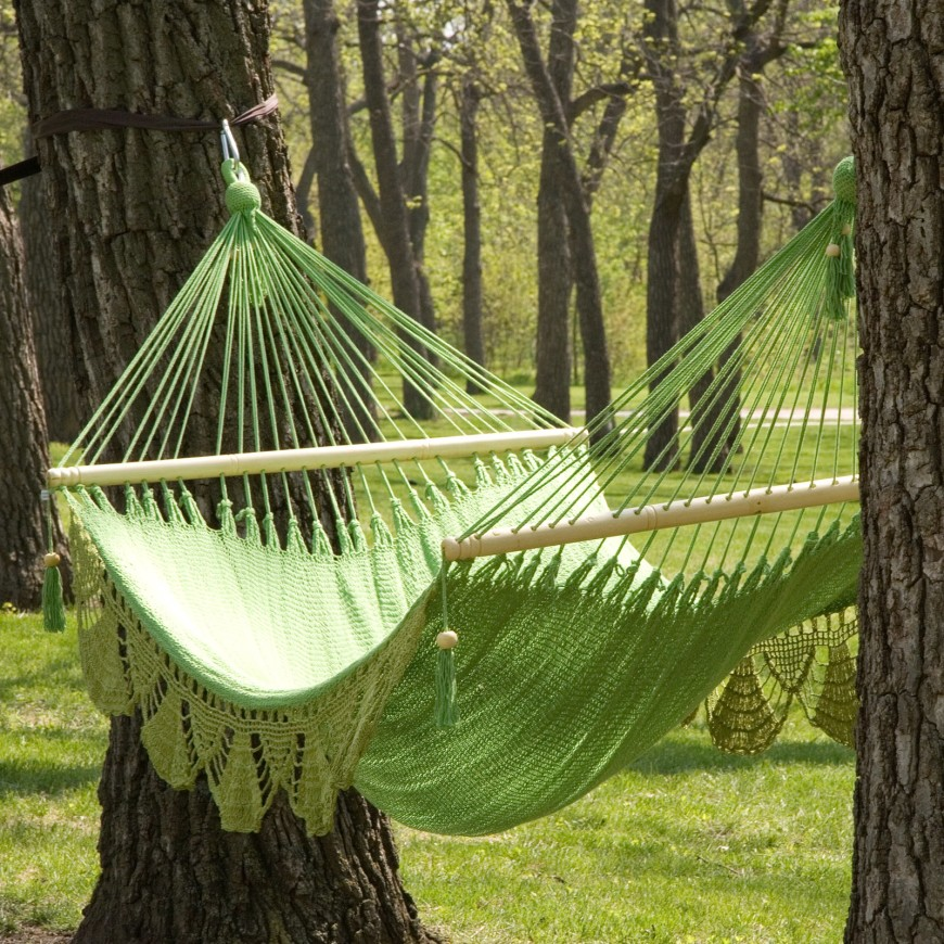 A Lovely Crocheted Hammock In Light Spring Green Suspended Between Two Sturdy Mature Trees