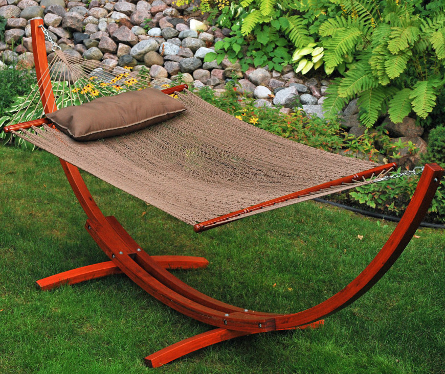 This bright red cedar wood frame hosts a flat woven spreader-bar hammock, and can easily fit anywhere in a backyard.