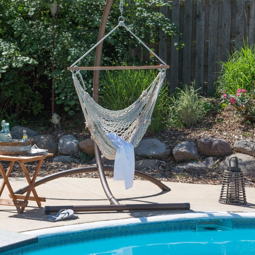 This crocheted hammock chair sits on the edge of the pool suspended from a metal frame. It's a cozy way to enjoy the poolside.