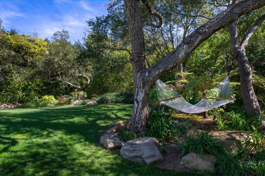 A simple, loose weave hammock hangs between two oak trees over a landscaped section of the yard looking out over the grass.
