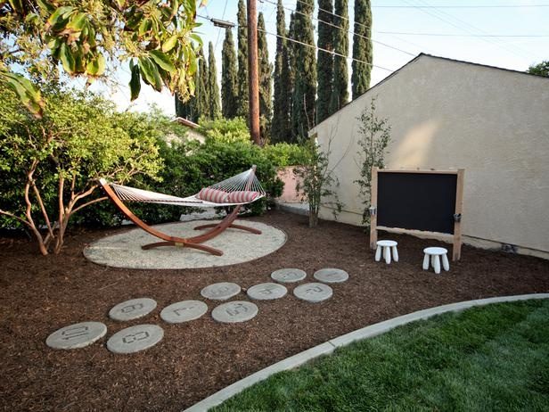 A small spot is sectioned off in this landscaping bed for a large hammock big enough for two. Nearby is a hopscotch area and a chalkboard.