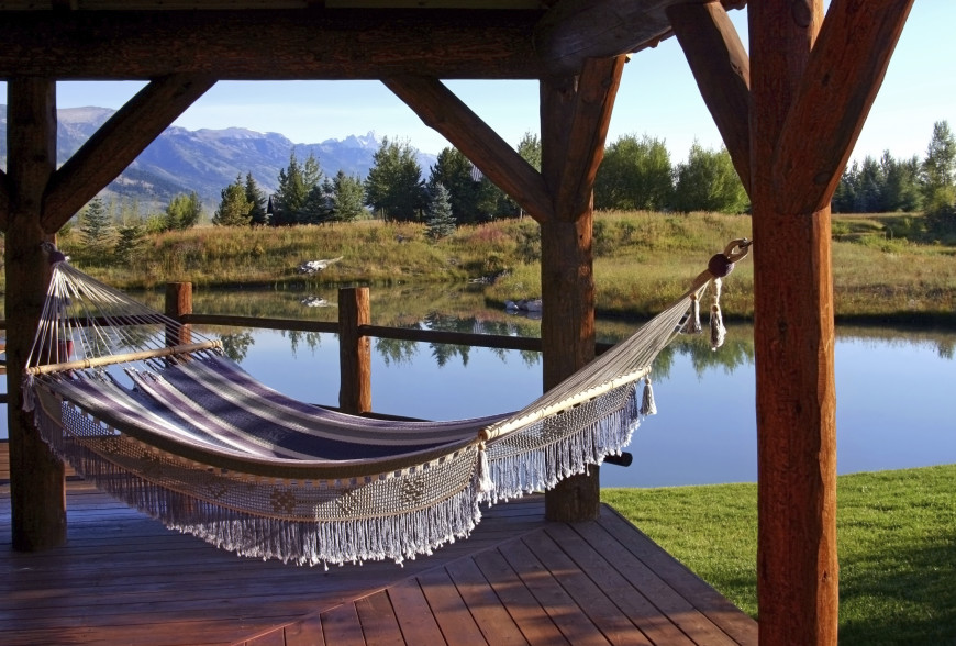 Woven hammock on a covered patio overlooking a private, quiet lake.