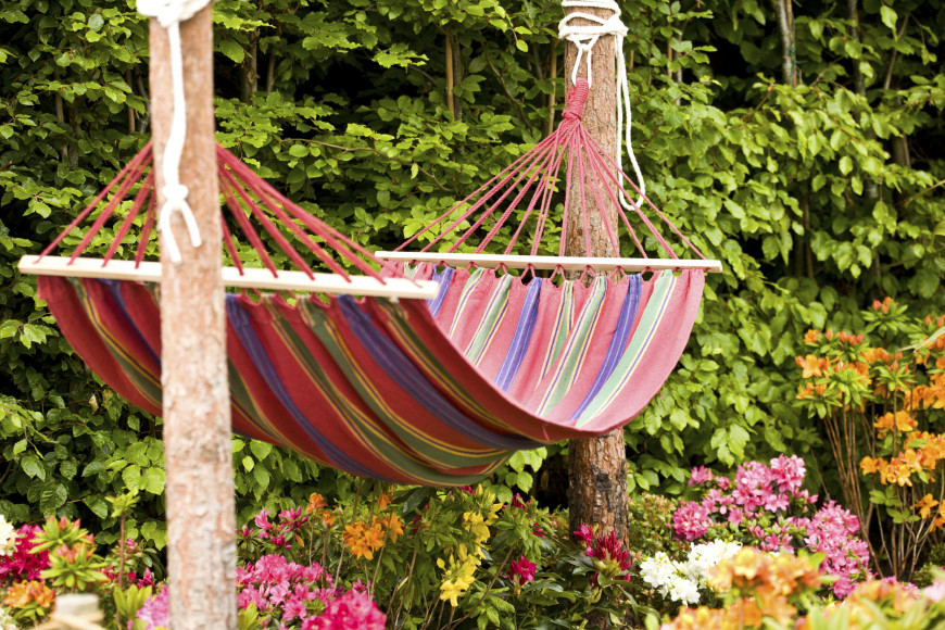 This colorful spreader-bar hammock is gorgeous against the blooming, bursting garden. This hammock is suspended between two skinny, but sturdy pine trees.