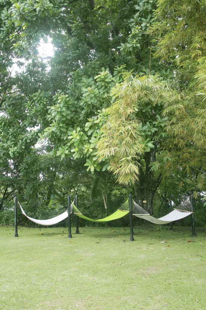 A trio of hammocks suspended from poles. This is perfect if you have kids always bickering over who gets to lay in the hammock.