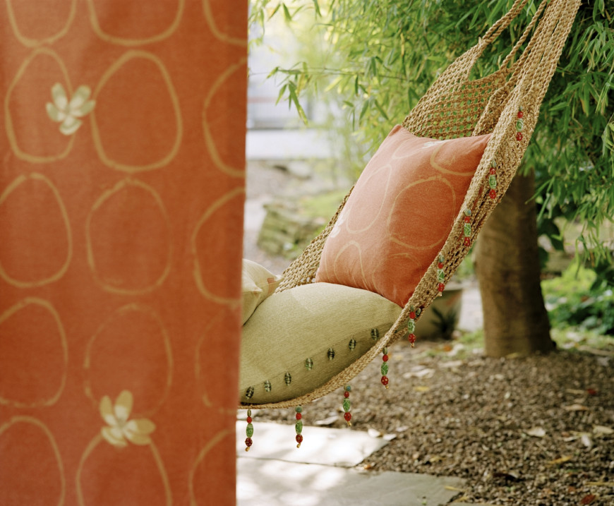 A woven hammock trimmed with strings of beads and made more cushioned with accent pillows.