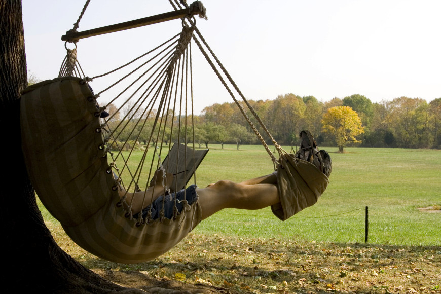 This unique hammock chair has a built-in foot rest mechanism for an arm-chair type outdoor seat.