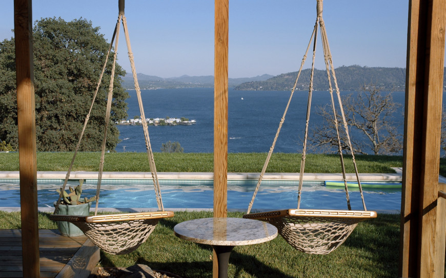 A swing-set type structure holds two bucket hammock swings with a table between. The seats look over the pool and onto the body of water in the distance.