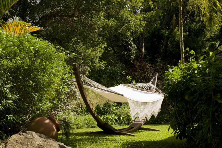 The delicate arch of the wooden base gives this hammock an ark-like look. The lacey pattern on the sides gives it a more feminine cast.