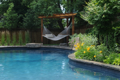 Another hammock suspended between the supports of a pergola structure at the edge of a pool.
