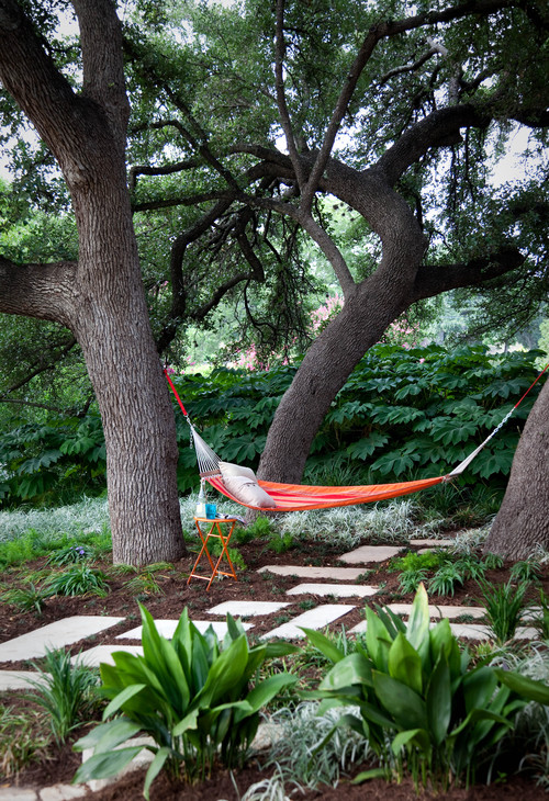 A brightly colored orange and white hammock positioned between two large oak trees. A flagstone path leads right up to and behind the hammock. A small table nearby is perfect for resting a glass of lemonade on.
