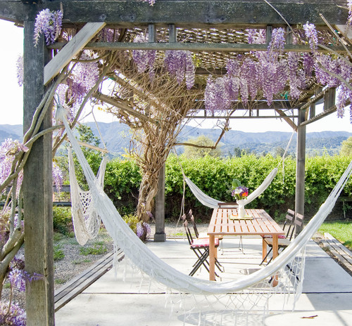 Thin, delicate white hammocks hang from three sides of this pavilion with a latticed roof. Beautiful lavender flowers hang from the top.
