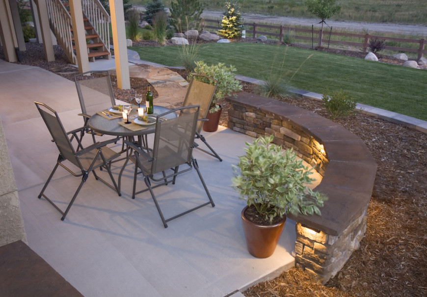 In this yard, there is a half wall dividing the patio from the rest of the yard. In the half wall, there is an installed step and a path lighting. This not only illuminates the patio with ambient light but also highlights potential trip hazards that would otherwise be hard to see at night.
