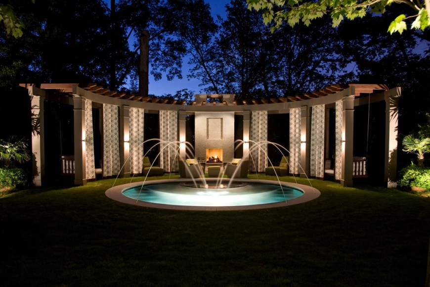 Sconce lighting is a great addition to structures like archways. The sconce lighting casts light upward at the structure and down at footpaths. In this picture there are also light fixtures in the fountain which highlight this stunning feature.