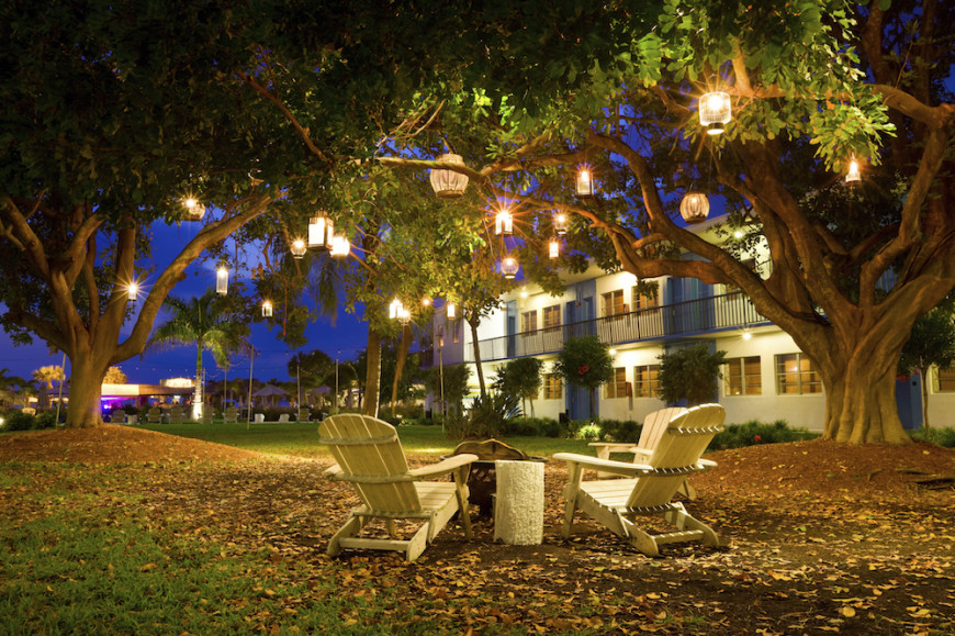 One creative idea is to hang various contrasting lanterns from trees. In this picture, various lanterns hang around the space to create a floating-light effect. This can be a magical aesthetic.