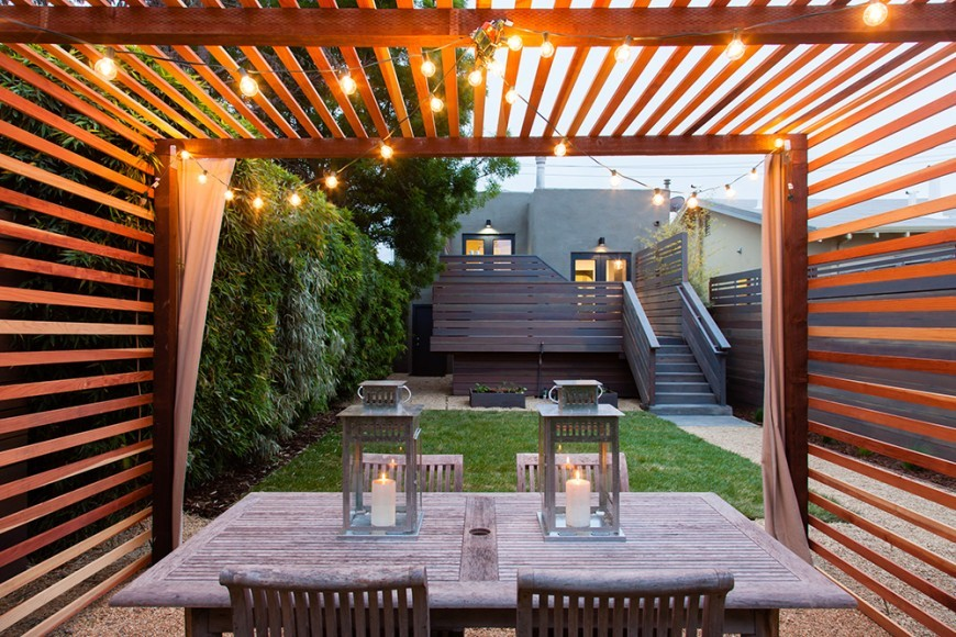 Here is an overhang with a string of bulbs hanging down over a table and chairs. These bulbs create a close and intimate atmosphere for a nice dinner outside.