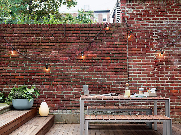 A string of bulbs looks great draped against a wall. The wall can be used as a backdrop to reflect the light back out into the area.