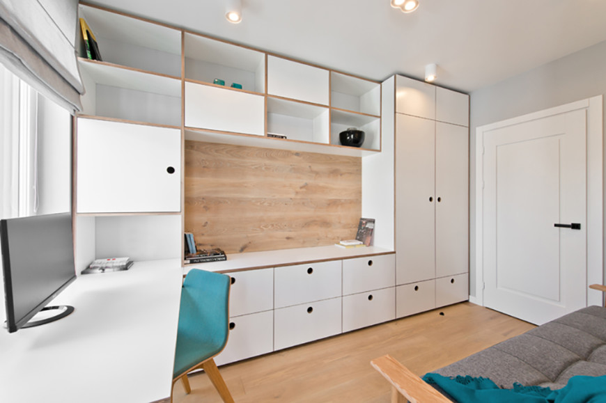 """The home office is awash in storage and shelving options, with cabinetry and open cupboards covering an entire wall. The built-in desk meets a countertop and natural wood """"backsplash"""" while a singular blue chair and blanket offer a small burst of color."""