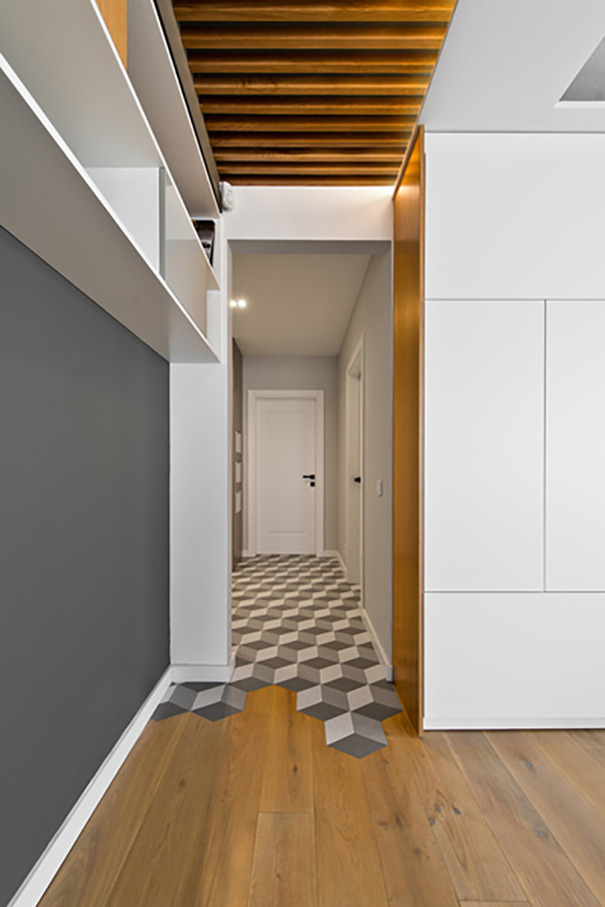 The open strip of natural wood ceiling panels leads toward the hallway, with its flooring covered in more geometric decals. To the right, more subtly built-in storage options appear in white.