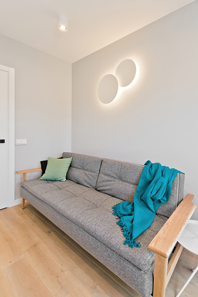 This modern minimalist futon brings a load of comfort and style to the home office room. Above is a unique modern sconce, appearing as a pair of circles glowing on the wall.