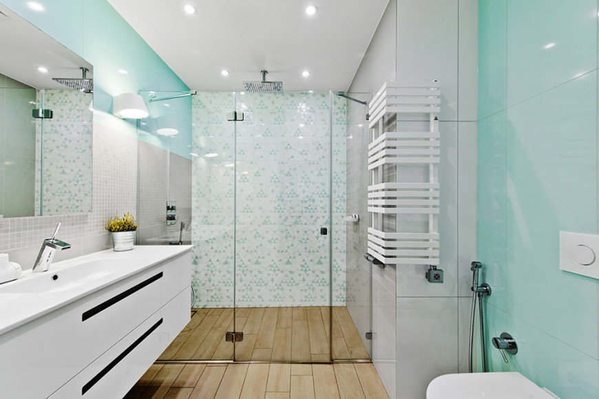 The bathroom is a subtle riot of textures, with the hardwood flooring meeting triangular patterned walls, glowing blue tile, and a floating vanity in white. The all-glass walk in shower fills in the entire end of the room.