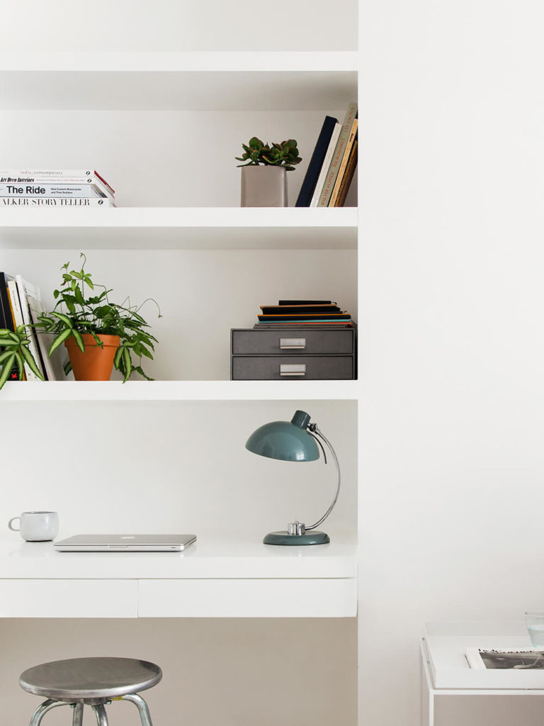 A cozy home office space features a built-in desk and abundant shelving, all in white and meshing perfectly with the walls. Subtle instances of color and chrome spike the minimalist palette.