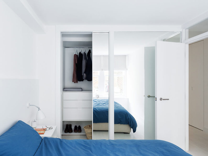 The bedroom makes use of large wall-size mirrors to help visually expand its size. A small window over the doorway extends the connectivity through to the rest of the home.