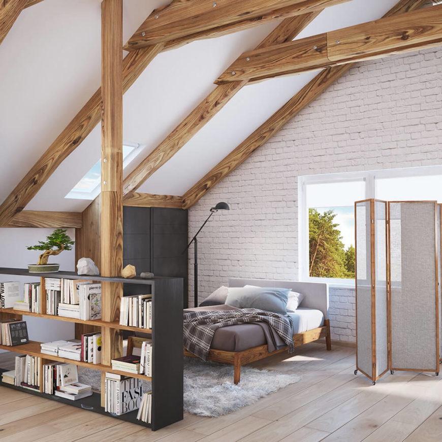 The bedroom is defined by a large bookshelf and free standing screen. With a natural wood bed frame that matches the exposed beams, there's an unmistakable cohesion at play here.