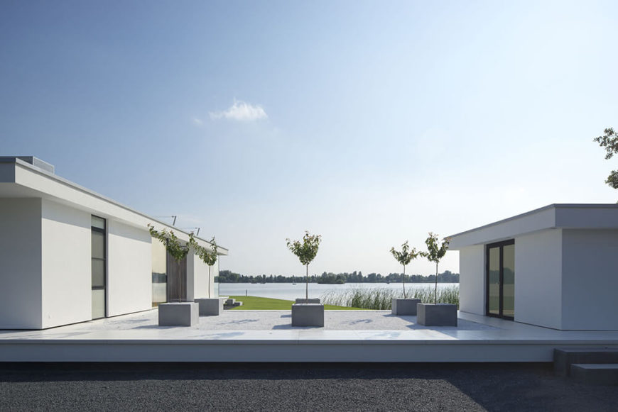 The segmented nature of the home makes a perfect opportunity for this expansive patio, situated between the main building and the guest house/garage. A minimalist set of container gardens houses a series of small trees between the sleek white structures.