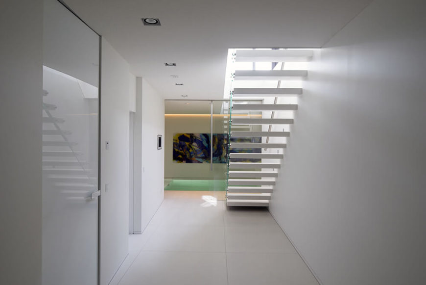 On the lower level, we see large format tile flooring, more pure white walls, and glossy door surfaces. At the end of this hall we see the interior jacuzzi room.