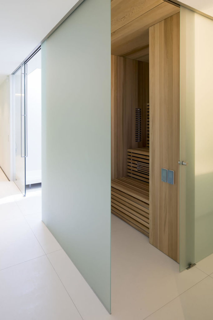 Here's a glimpse of the in-home sauna, wrapped in smoked glass and flush with rich wood paneling. It's a rare burst of natural elements within the sleek modern structure.