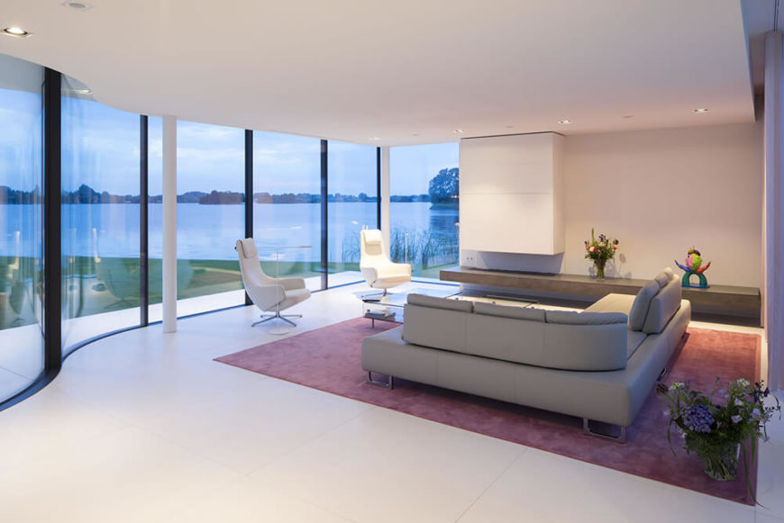The living room introduces a blush of color to the interior, with a large red area rug holding the sleek leather sectional. From here, we see the expansive nature views afforded by the gently curved exterior glass.