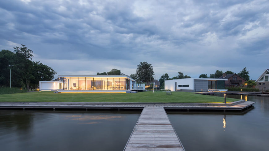 Viewed from on the lake itself, we see the glowing interior through the completely open back side of the home. The living experience here is deeply integrated with the environment.