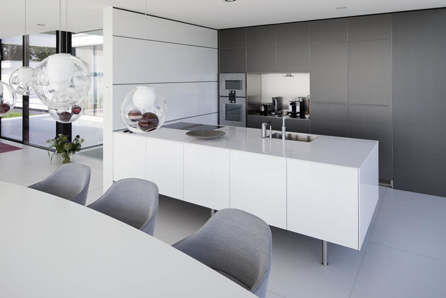 The kitchen is defined by this sleek white island and minimalist cabinetry, allowing for an abundance of storage to be hidden out of sight. The dining table is lit by a set of glass bulb pendant lights.