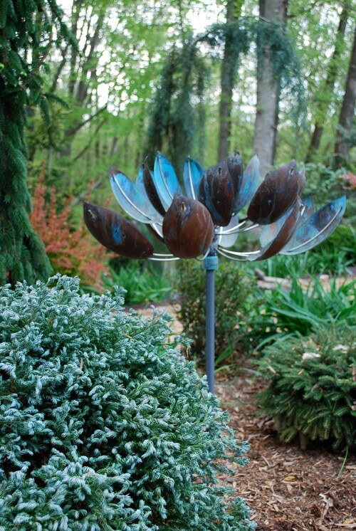 Some sculptures bring style and color to a garden. The blue metal flower has an industrial look that blends the shape and color of nature with very manmade materials.