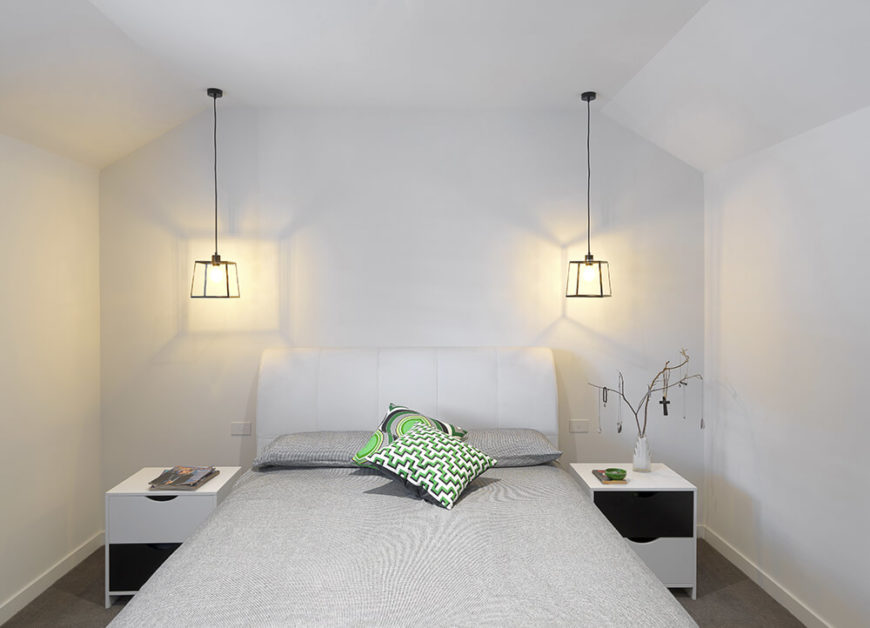 The master bedroom stands in the same minimalist style as the open plan living and dining room area. White walls stand over grey carpet and a grey toned bed, flanked by a pair of white bedside tables and metal frame pendant lights.