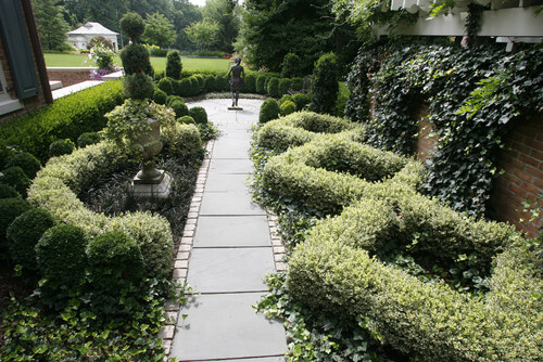 Here are some well maintained hedges making fancy shapes along this path leading to a statue. Hedge sculptures have a way of bringing some elegance and high end appeal to a garden.