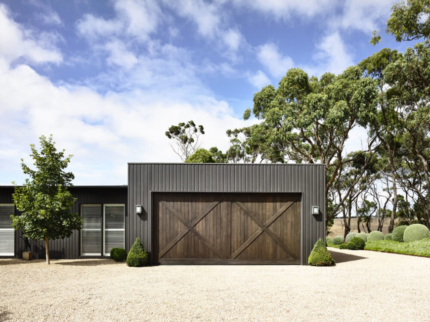 The garage helps maintain that farmhouse look with large cross-beam doors in a dark coffee brown tone. All around, we can see the carefully crafted hedges and sculpted bushes surrounding the home.