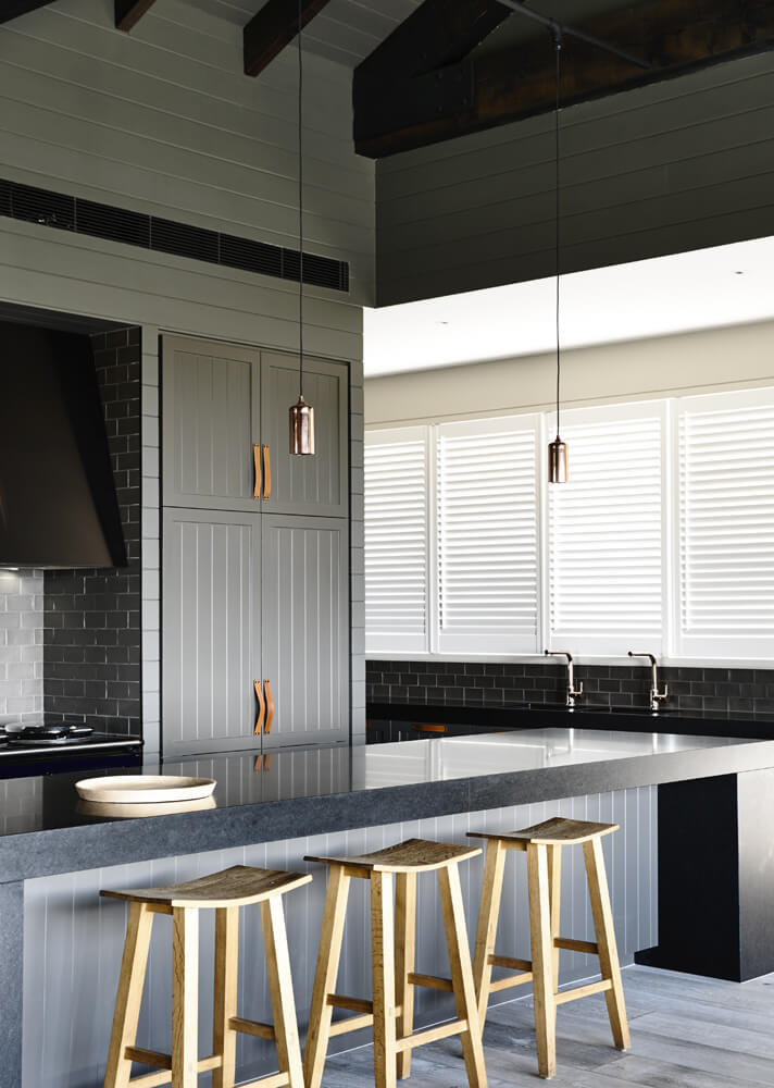 The kitchen is defined by this massive black slab topped island, with abundant space for in-kitchen dining. The sleek minimalism is buffered by grey subway tile walls.