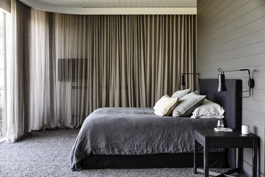 The master bedroom also features massive floor to ceiling windows, which necessitated the inclusion of wraparound curtains for privacy and darkness. The muted color scheme appears here unbroken.