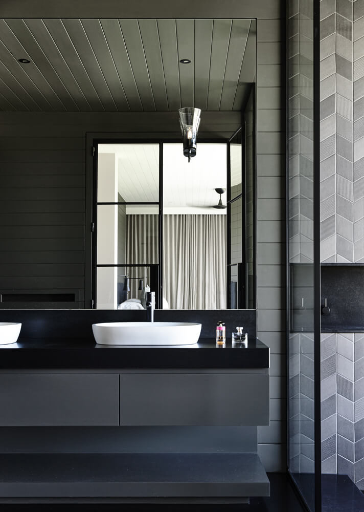 The bathroom sports similarly sleek, black countertops as the kitchen, plus intricate tile work and a splash of brightness, courtesy of the white porcelain vessel sinks.