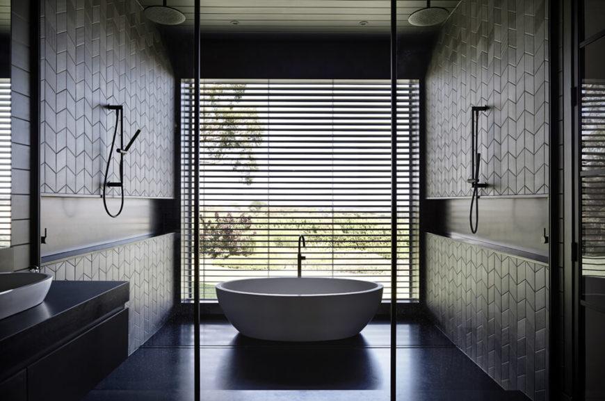 The master bathroom centers on this huge bathing area, a small room within a room containing shower function and a bold white pedestal tub. The huge window provides exquisite views from the bath while shades keep privacy.