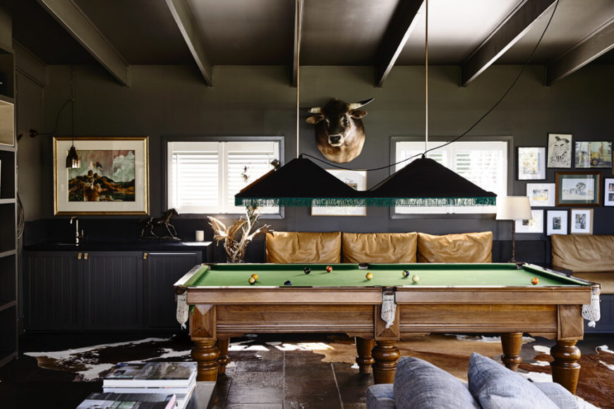 The home also boasts a touch of luxurious relaxation with this space, centered on a traditionally styled billiards table. Above, we see a slimmer take on the exposed ceiling beams.